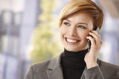 Mulher de negócios feliz que fala no móbil fora Imagens de Stock Royalty Free