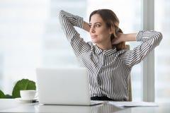 A mulher de negócios feliz que guarda as mãos atrás da cabeça terminou descansar no local de trabalho imagem de stock