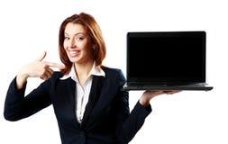 Mulher de negócios feliz que guarda o portátil e que aponta nele foto de stock royalty free