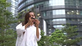 Mulher de negócios feliz que joga o jogo no smartphone durante sua ruptura vídeos de arquivo