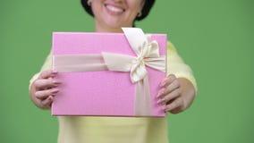 Mulher de negócios feliz que sorri ao dar a caixa de presente filme