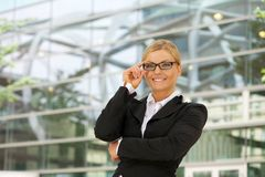 Mulher de negócios feliz que sorri com vidros na cidade Fotos de Stock Royalty Free