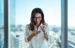 Mulher de negócios feliz que usa seu telefone celular no escritório imagem de stock royalty free