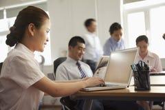Mulher de negócios focalizada que trabalha em seu portátil no escritório Fotos de Stock