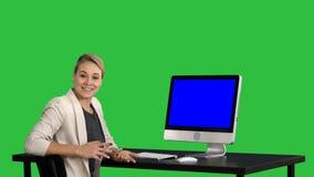 Mulher de negócios focalizada segura que fala à câmera e que olha para monitorar perto dela em uma tela verde, chave do croma azu filme