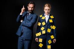 Mulher de negócios forçada com notas pegajosas na roupa que está perto do homem de negócios farpado que aponta acima com dedo fotografia de stock