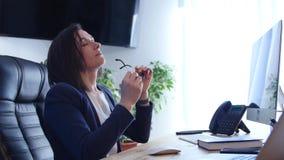 Mulher de negócios forçada que trabalha em sua mesa no trabalho filme