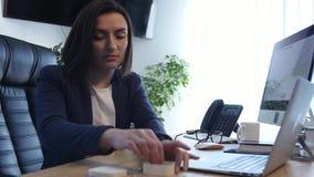 Mulher de negócios forçada que trabalha em sua mesa no trabalho video estoque