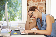 Mulher de negócios forçada Working At Computer no escritório moderno Imagens de Stock Royalty Free