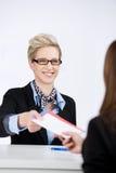 Mulher de negócios Giving Traveling Documents ao recepcionista foto de stock
