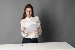 A mulher de negócios guarda os papéis em suas mãos e lê o que é escrito lá no fundo cinzento Fotografia de Stock Royalty Free