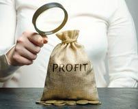 A mulher de negócios guarda uma lupa sobre um saco do dinheiro com o lucro da palavra Análise do orçamento na empresa rendimento imagem de stock