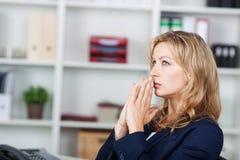 Mulher de negócios With Hands Clasped que olha afastado no escritório imagem de stock royalty free