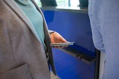 Mulher de negócios Holding Mobile Phone e passaporte no aeroporto Recep Imagem de Stock