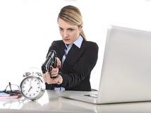 Mulher de negócios irritada furioso que trabalha apontando a arma ao despertador dentro fora do conceito do tempo Imagens de Stock