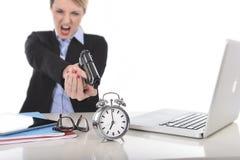 Mulher de negócios irritada furioso que trabalha apontando a arma ao despertador dentro fora do conceito do tempo Imagens de Stock Royalty Free