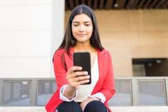 Mulher de negócios latino-americano Social Networking On seu telefone celular imagens de stock