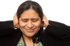 Mulher de negócios latino-americano In Stress Takes fora dos auriculares imagens de stock royalty free