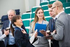 Mulher de negócios Laughing While Colleagues que discute na leitura Ha Imagens de Stock Royalty Free