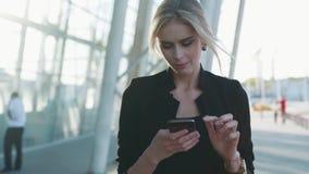 A mulher de negócios lindo com penteado formal passa com pressa o terminal de aeroporto, texts a mensagem em seu telefone vídeos de arquivo