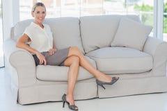 Mulher de negócios loura atrativa que levanta o assento no sofá foto de stock royalty free