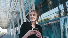 A mulher de negócios loura bonita com composição natural anda pelo centro de negócio, texts a mensagem em seu telefone vídeos de arquivo