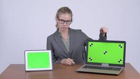 Mulher de negócios loura bonita nova que fala ao mostrar o portátil e a tabuleta digital vídeos de arquivo
