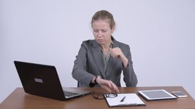 Mulher de negócios loura bonita nova que usa o portátil e examinando chocado o trabalho video estoque