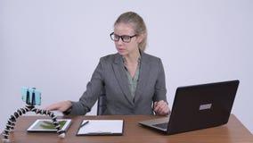 Mulher de negócios loura bonita nova que vlogging e que explica algo no trabalho video estoque