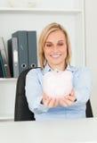 Mulher de negócios loura bonito que prende um banco piggy Imagem de Stock Royalty Free