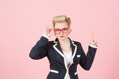 Mulher de negócios loura com vidros vermelhos que aponta acima pelo dedo no fundo cor-de-rosa imagem de stock