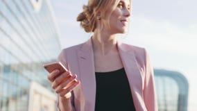 A mulher de negócios loura lindo no equipamento à moda cor-de-rosa passa pelo centro do airportbusiness, usa seu telefone e vídeos de arquivo