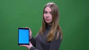 A mulher de neg?cios loura nova mostra a tela azul do croma da tabuleta isolada no fundo verde do chromakey video estoque