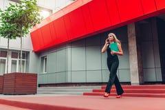 Mulher de negócios loura nova que chama o smartphone e que guarda o dobrador que anda pelo centro de negócios na cidade Communiat imagem de stock
