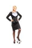 Mulher de negócios loura nova que levanta com uma bola de futebol Fotografia de Stock Royalty Free