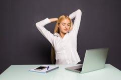 Mulher de negócios loura que olha o trabalho no laptop com satisfação e que estica os braços no ar Fotos de Stock
