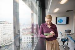 Mulher de negócios loura que trabalha na tabuleta no escritório imagem de stock royalty free