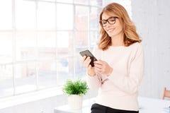 Mulher de negócios madura atrativa que usa seus telefone celular e envio de mensagem de texto fotografia de stock