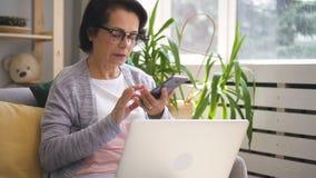 A mulher de negócios madura está falando no telefone, usando o portátil que senta-se em casa filme