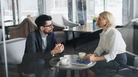 Mulher de negócios madura que discute o negócio com o sócio bem sucedido no café filme
