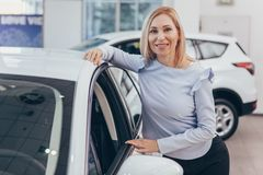 Mulher de negócios madura que escolhe o automóvel novo no negócio imagens de stock royalty free