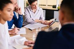 Mulher de negócios madura que mostra a seu colega masculino a informação analítica na tabuleta Imagens de Stock