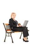Mulher de negócios madura que senta-se em um banco de madeira e em um trabalho Fotografia de Stock Royalty Free
