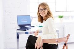 Mulher de negócios madura de sorriso que senta-se na mesa e em olhar de escritório a câmera imagem de stock royalty free