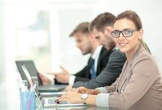 Mulher de negócios moderna bonita que trabalha com seus colegas sobre Imagens de Stock