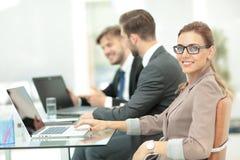 Mulher de negócios moderna bonita que trabalha com seus colegas sobre Fotos de Stock Royalty Free