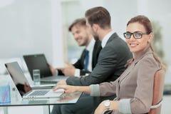 Mulher de negócios moderna bonita que trabalha com seus colegas sobre Foto de Stock Royalty Free