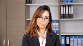 Mulher de negócios moreno bonita no escritório que sorri na câmera filme