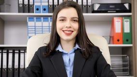 Mulher de negócios moreno bonita que sorri à câmera video estoque