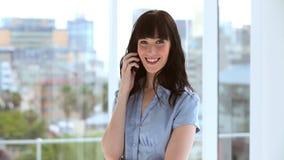 Mulher de negócios moreno feliz que usa seu telefone celular video estoque